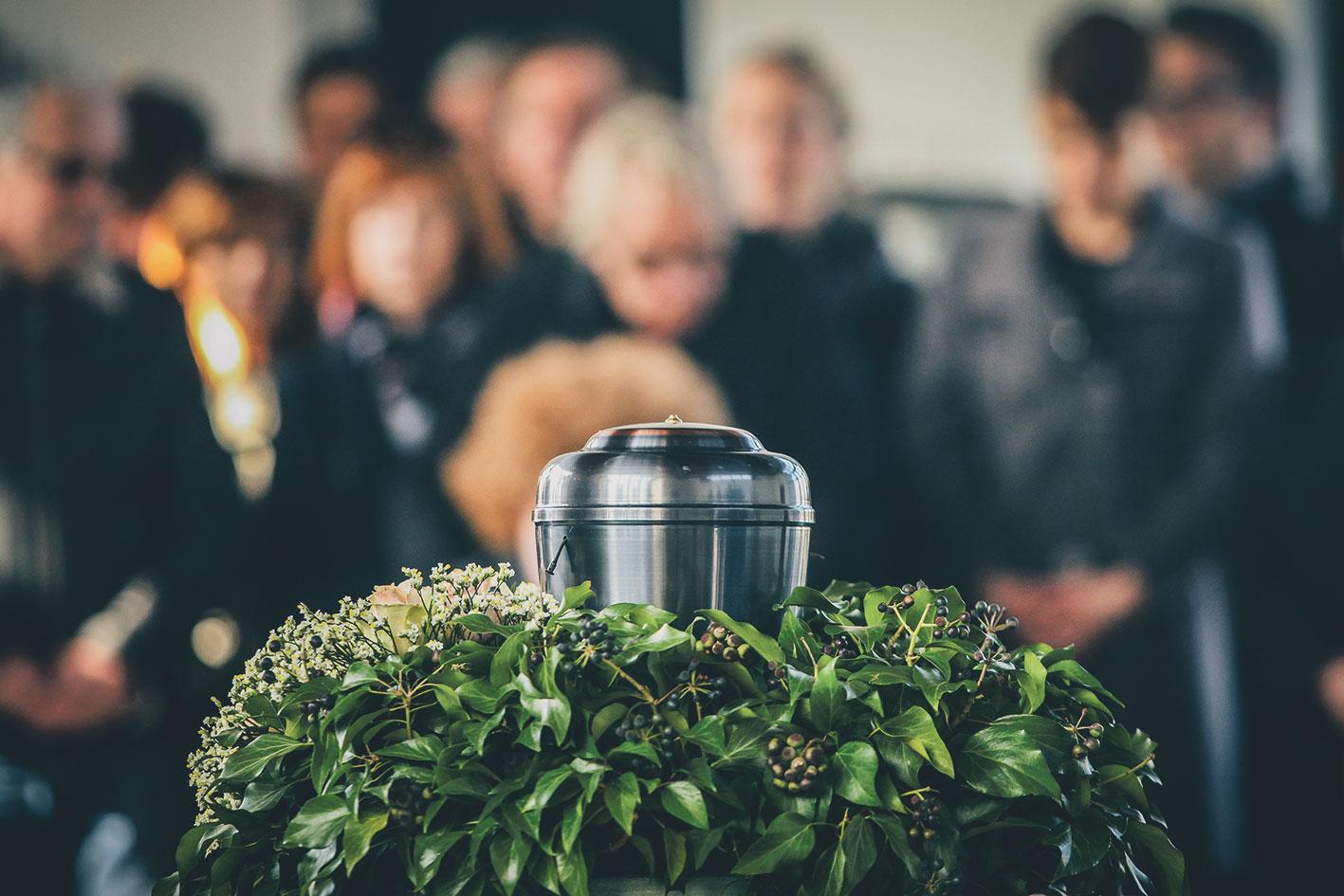 Urne mit Trauergemeinschaft im Hintergrund.