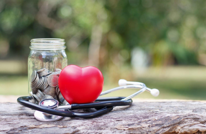 Ein Herz aus Schaumstoff neben einem Glas voller Münzen