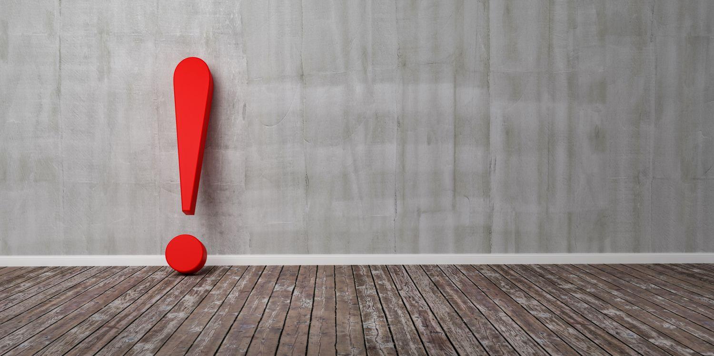 Rotes Ausrufezeichen als Gefahrenzeichen vor einer grauen Wand