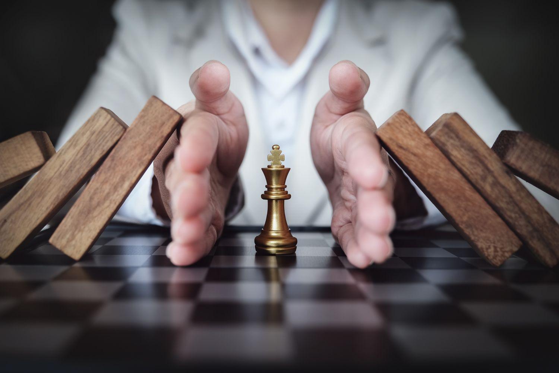 Schachfigur König, die vorm Fall geschützt wird.