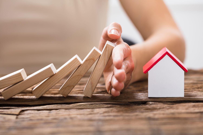 Auf ein Haus fallende Dominosteine werden von einer Hand aufgehalten. Thema: Was bei einer Hausratversicherung abgedeckt ist