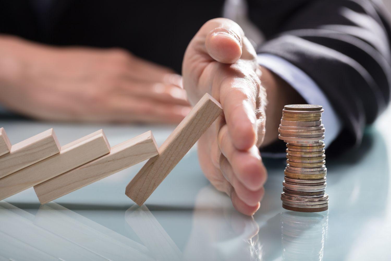 Dominosteine fallen auf einen Geldstapel. Eine Hand schützt ihn im letzten Moment.