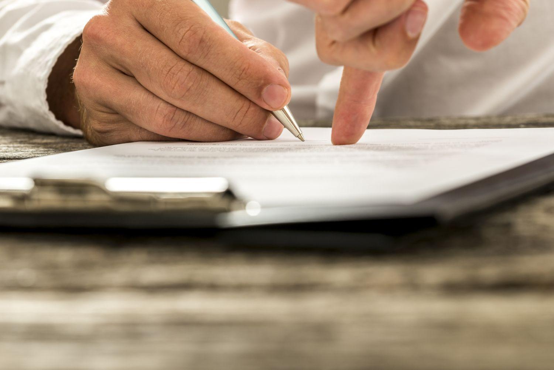 Jemand unterschreibt einen Vertrag. Thema: Krebsversicherung