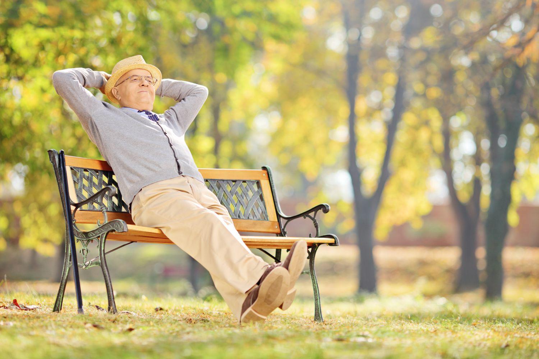 Ein älterer Mann sitzt auf einer Parkbank. Um die richtige Altersvorsorge muss er sich nicht mehr kümmern