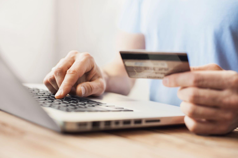 Jemand tippt am Laptop Zahlungsdaten ein. Thema: Versicherung abschließen
