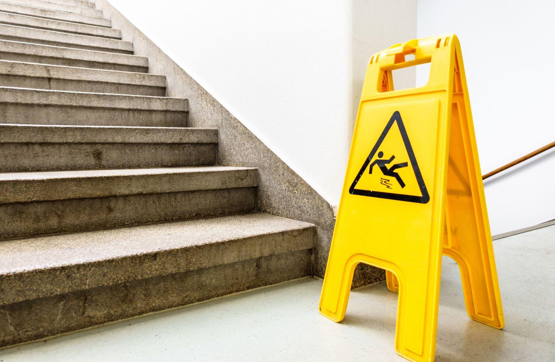 Warnschild vor einer frisch gewischten Treppe. Thema: Versicherungsschutz