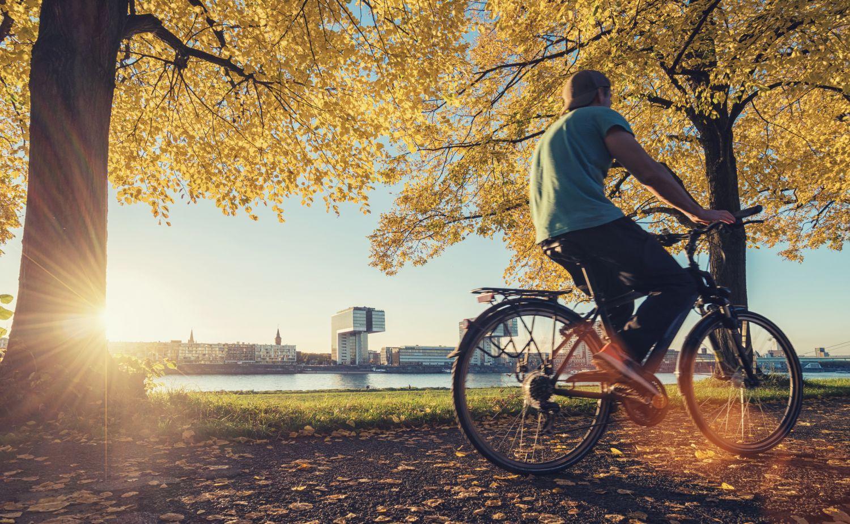 Junger Mann auf dem Fahrrad am Rheinufer